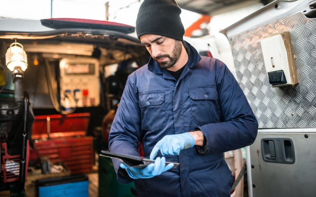 A service provider tracks inventory on his tablet while working out of a van.