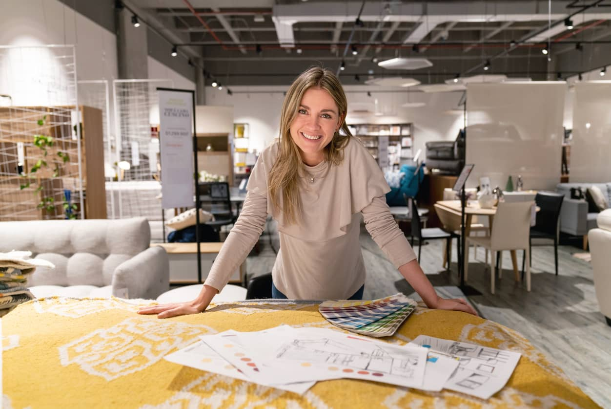 A female designer smiles while looking over plans for a project.