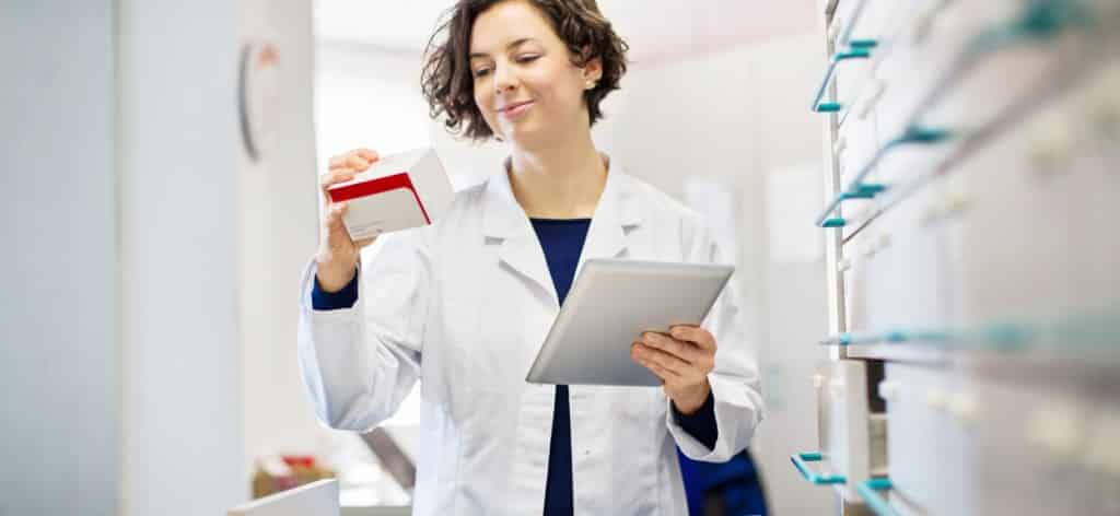 A healthcare provider uses a tablet to pull the correct medical product off a shelf.