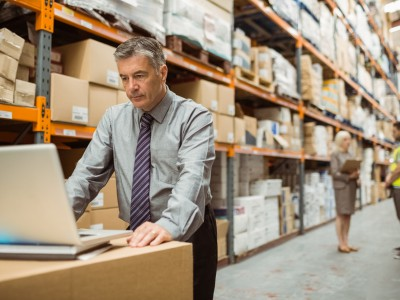 A warehouse manager uses a computer to track inventory