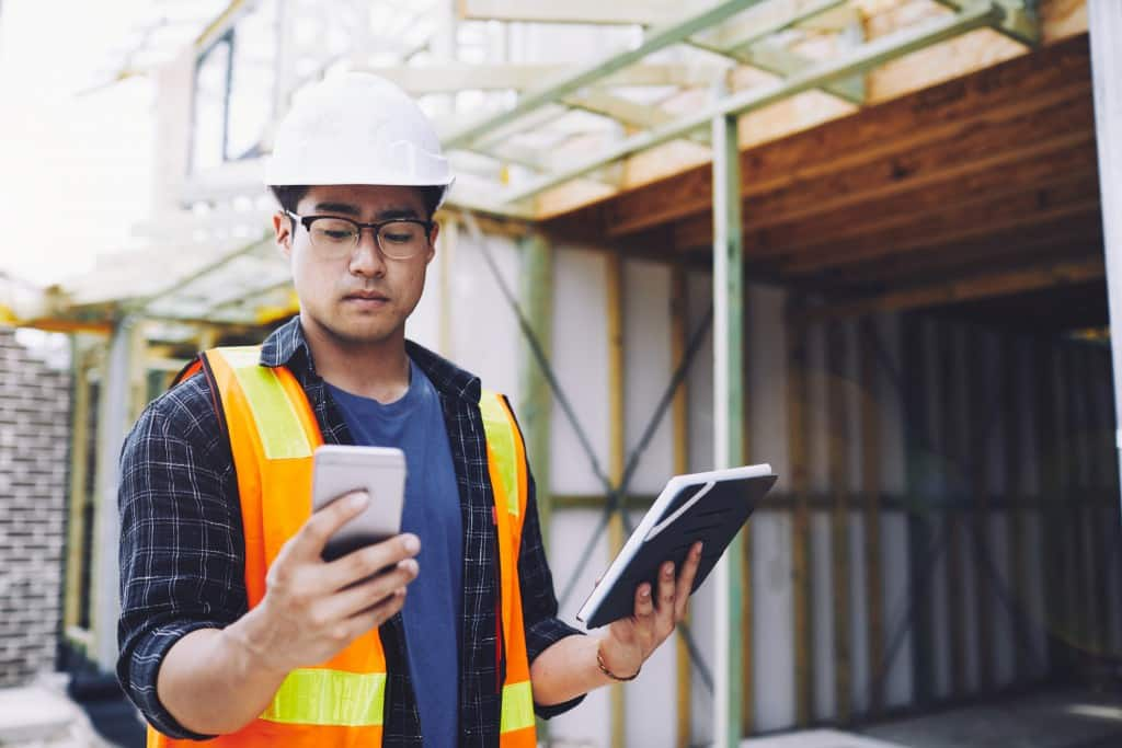 Construction worker takes inventory using wireless devices.