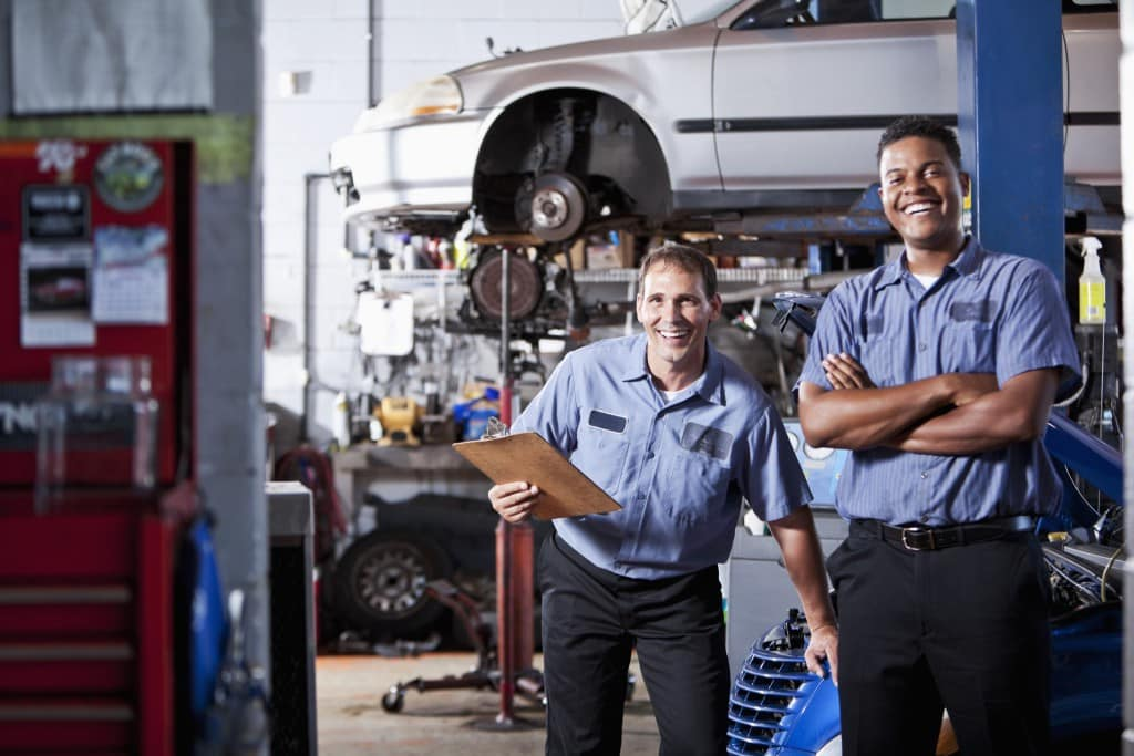 Two auto shop workers take inventory in a shop.