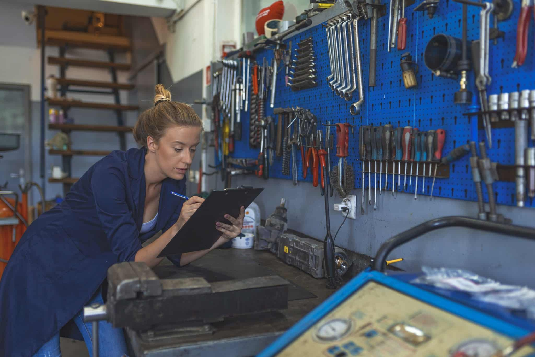 A woman takes inventory in an auto shop.