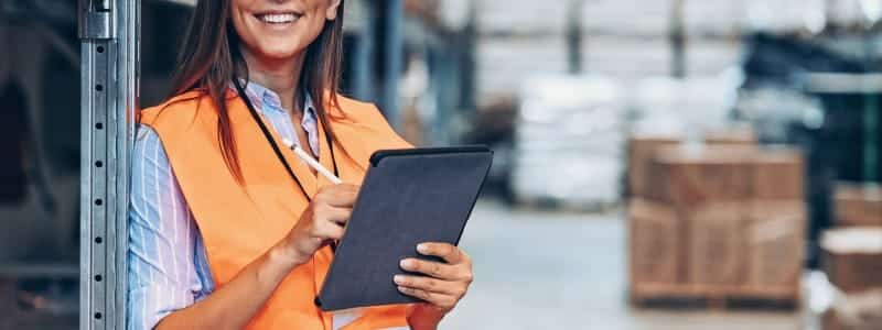 A warehouse manager takes inventory on a tablet.
