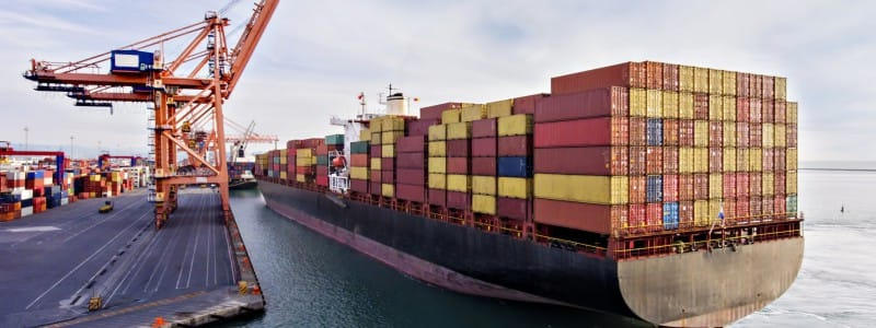 A boat with shipping containers arrives at a dock.
