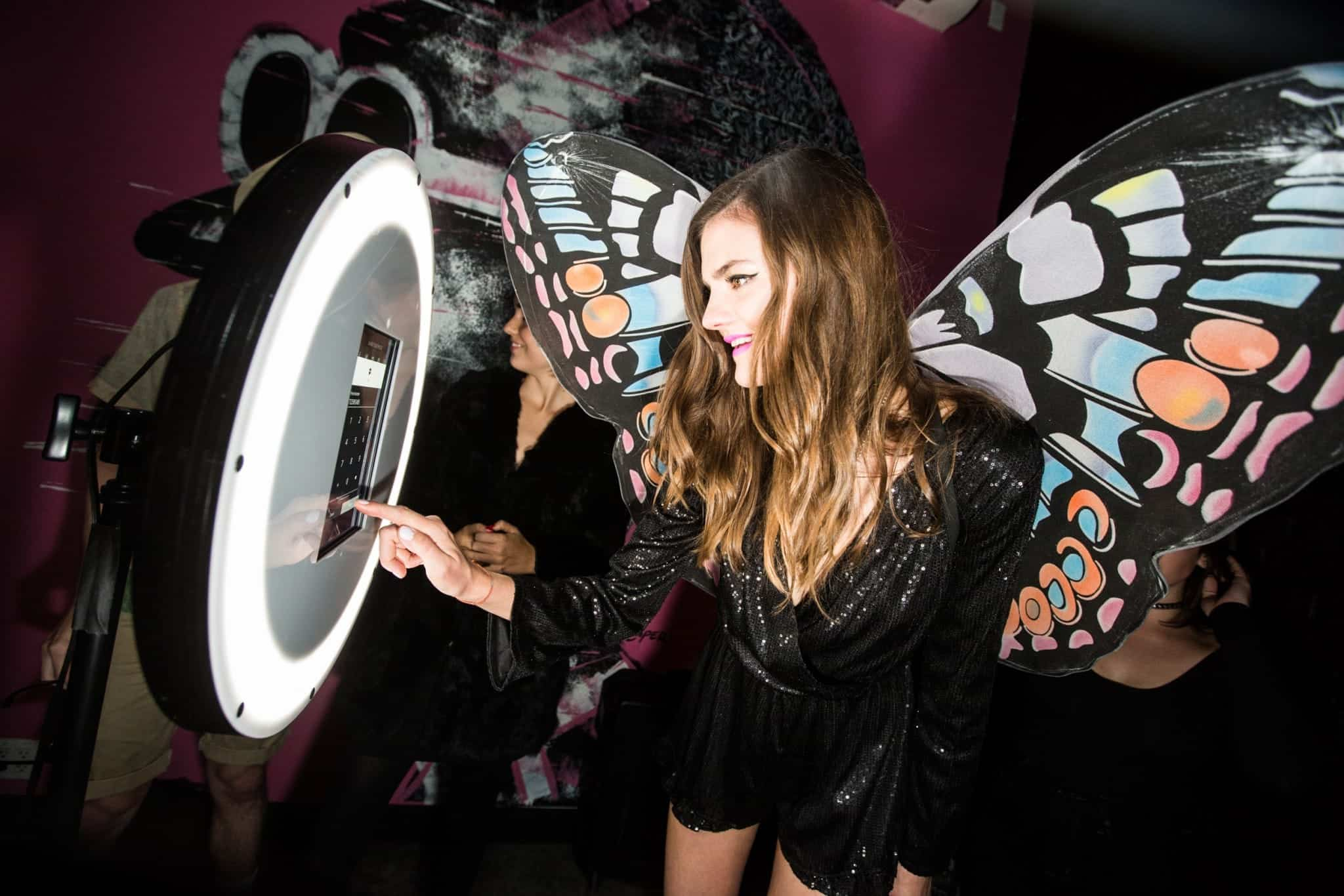 A woman wearing butterfly wings snaps a pic using modern technology.