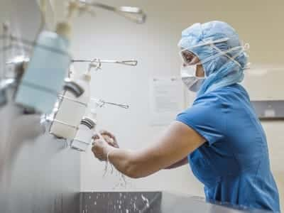 A doctor in scrubs and a face mask washes her hands.