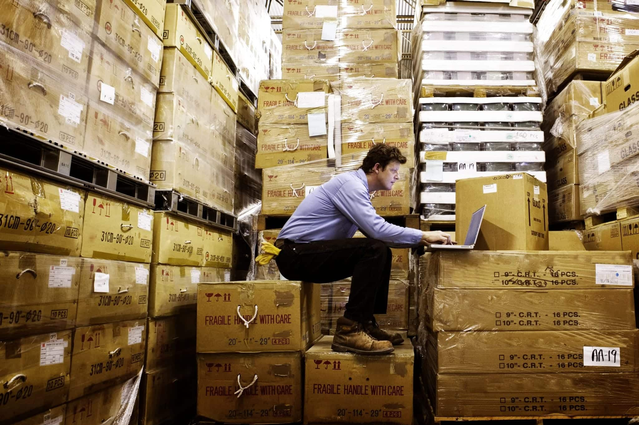 A man takes inventory while sitting on boxes in a warehouse.