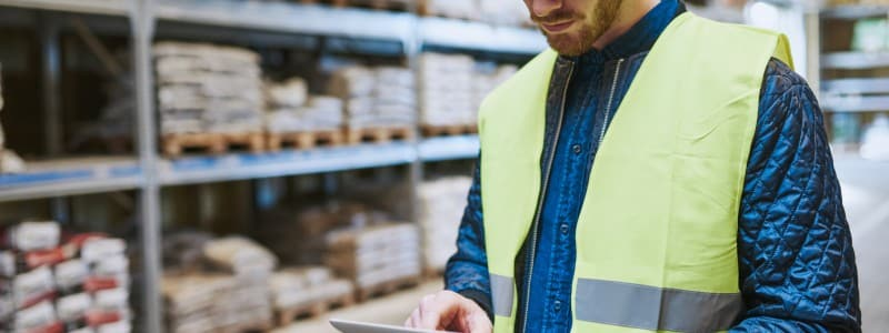 An employee wearing a visibility vest takes inventory on a tablet.