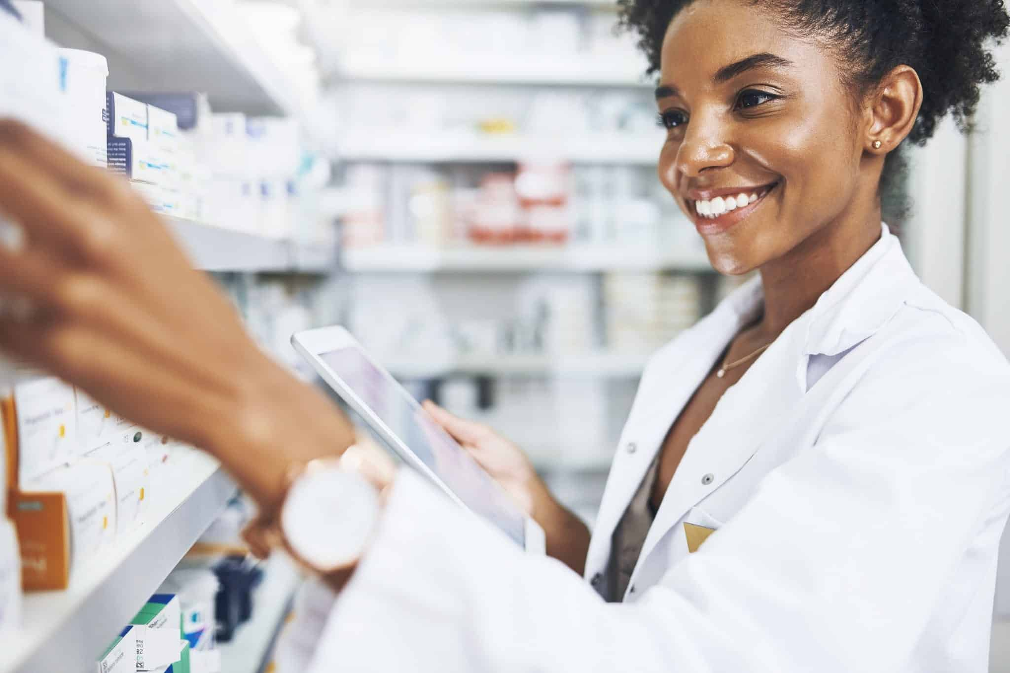A hospital pharmacist uses a tablet to inventory medicine.