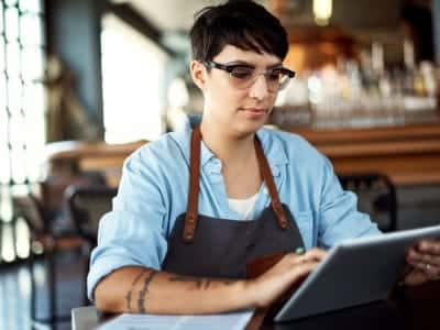 A woman working in a restaurant takes inventory on a tablet.