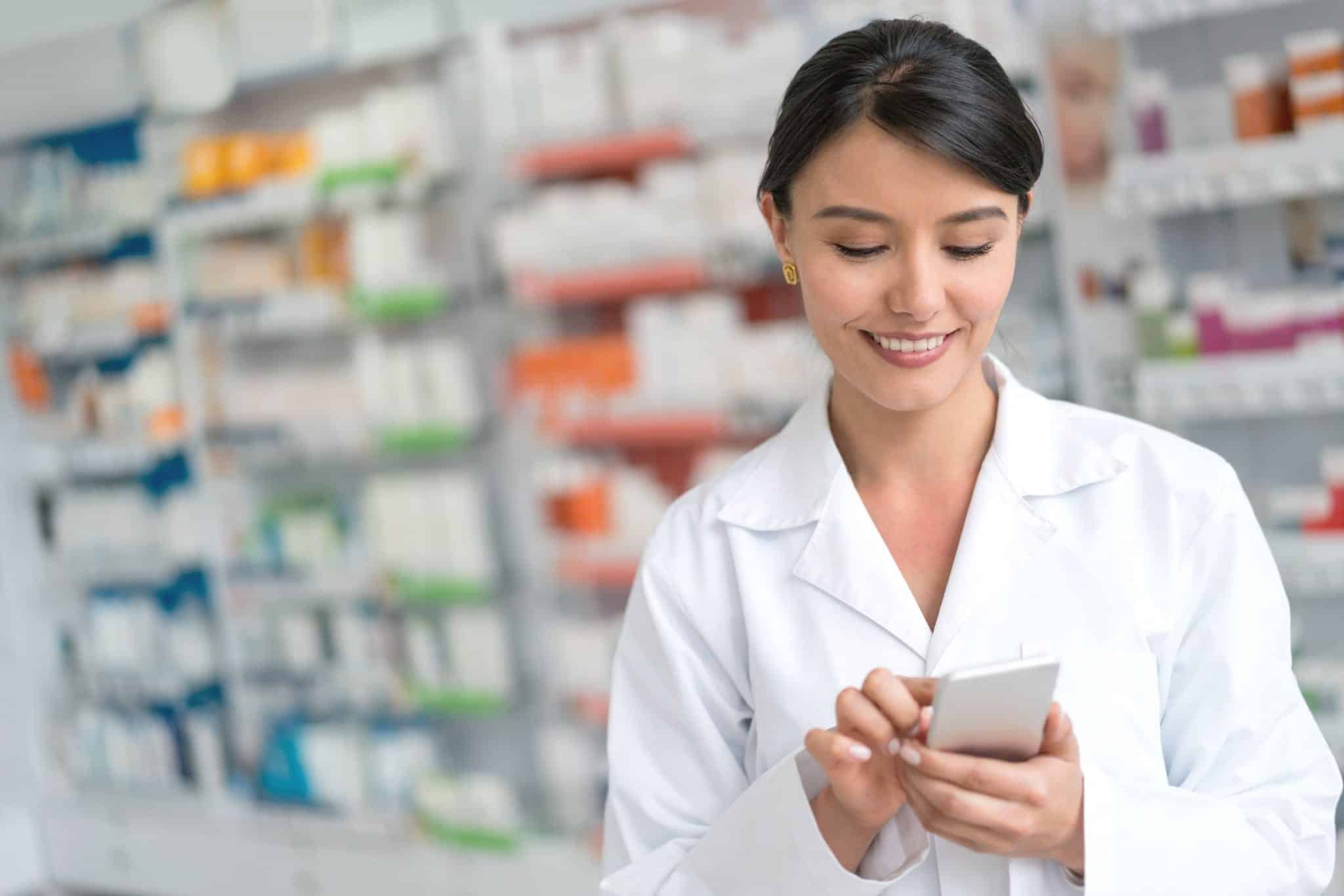 a female healthcare worker uses a phone with medical storage in background.