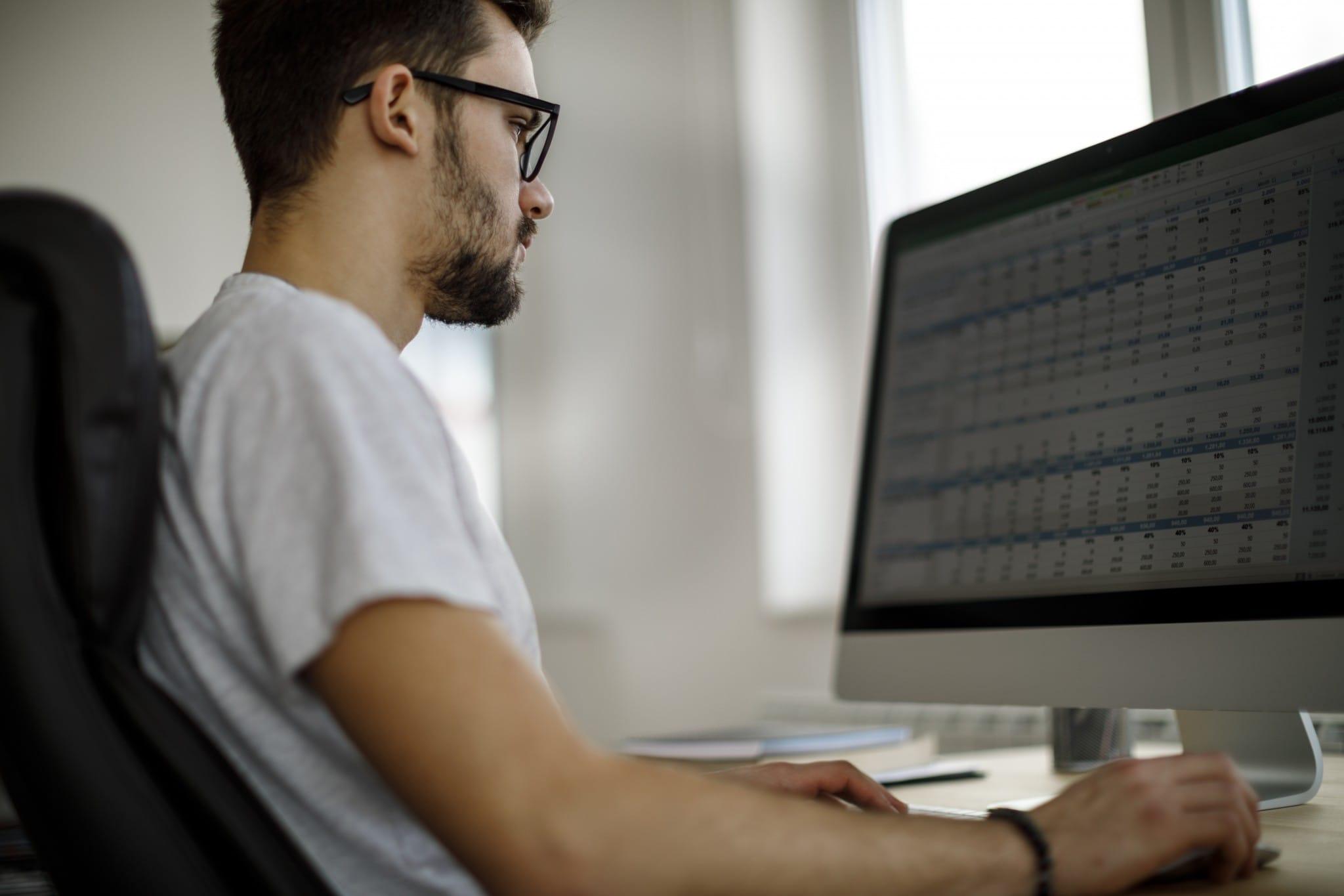 A man works on a spreadsheet at a desktop computer.