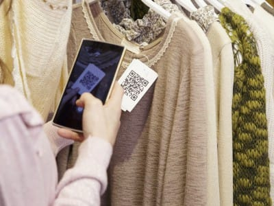 A woman scans a QR code from clothing.