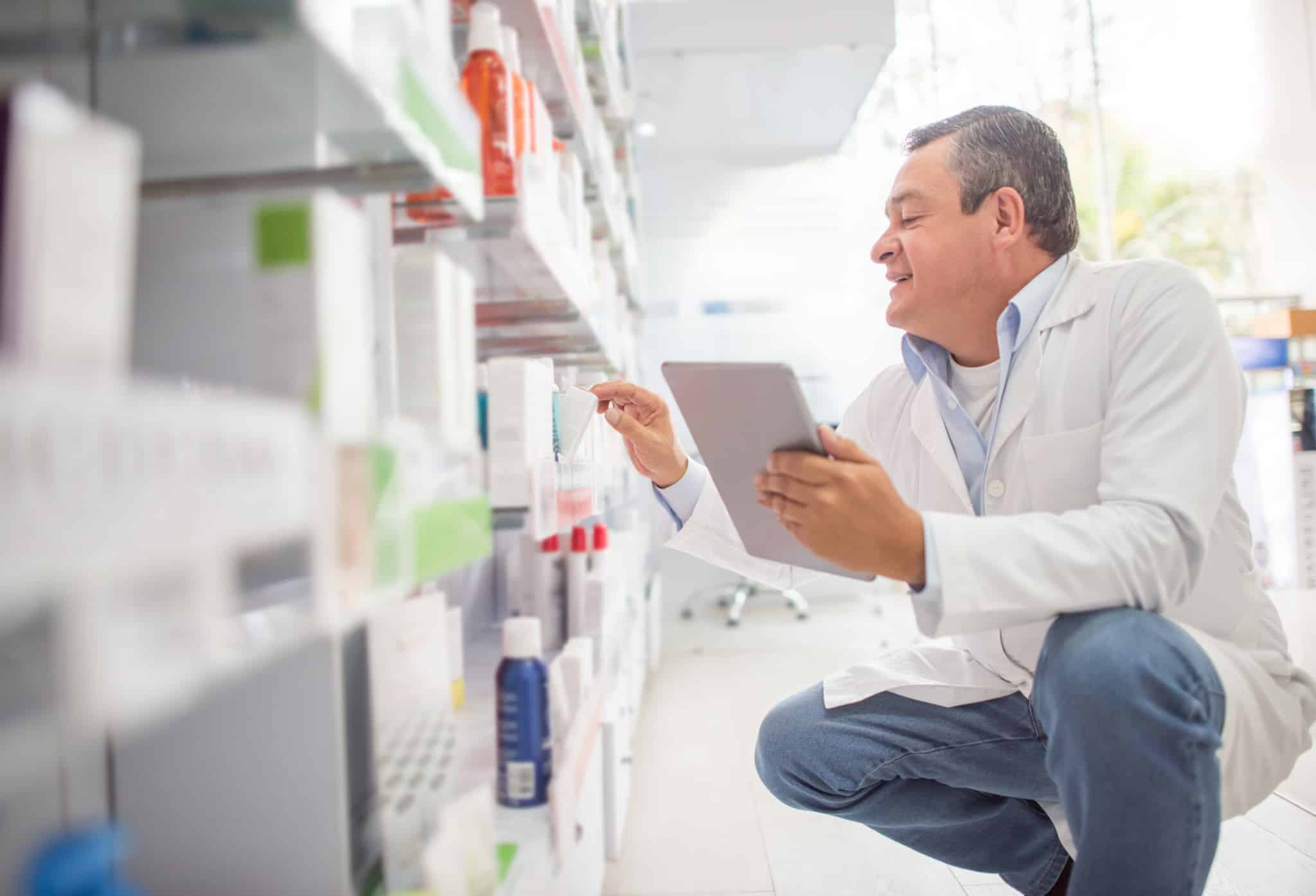 A man takes inventory on a tablet in a pharmacy.