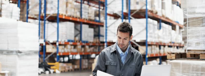 A man in a warehouse calculates inventory.