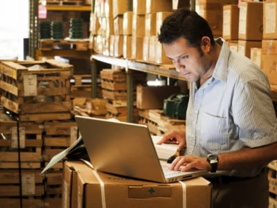 A man takes inventory in a stockroom using a laptop.