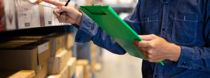 A person takes physical inventory on a clipboard.