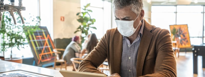 Businessman takes inventory using a tablet, while wearing a mask.