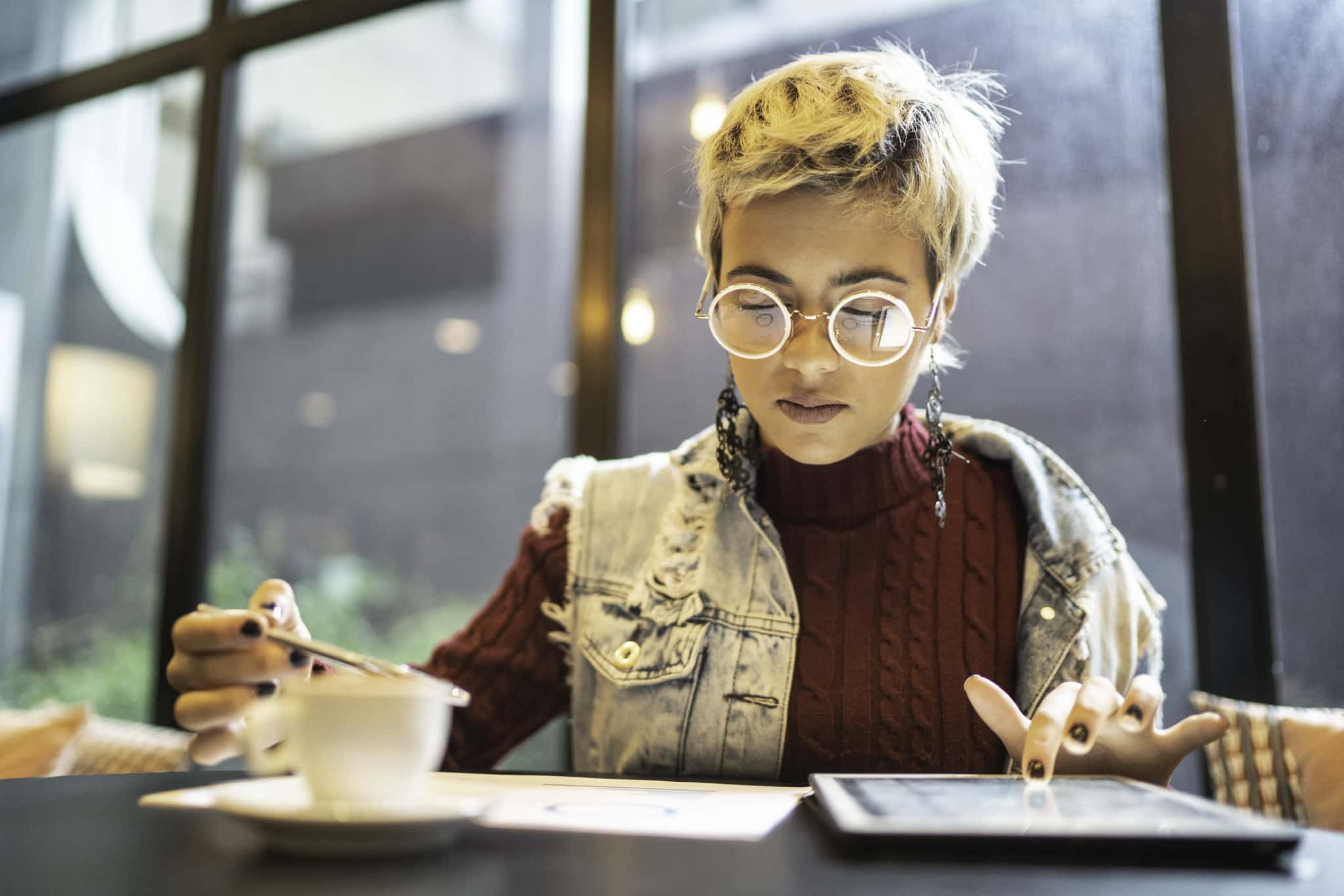 A woman reviews business reports on paper and on a tablet.