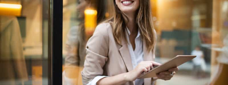 A woman smiles while using a tablet to review business information.