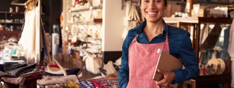 A woman in an apron holding a tablet works in her upholstery studio.