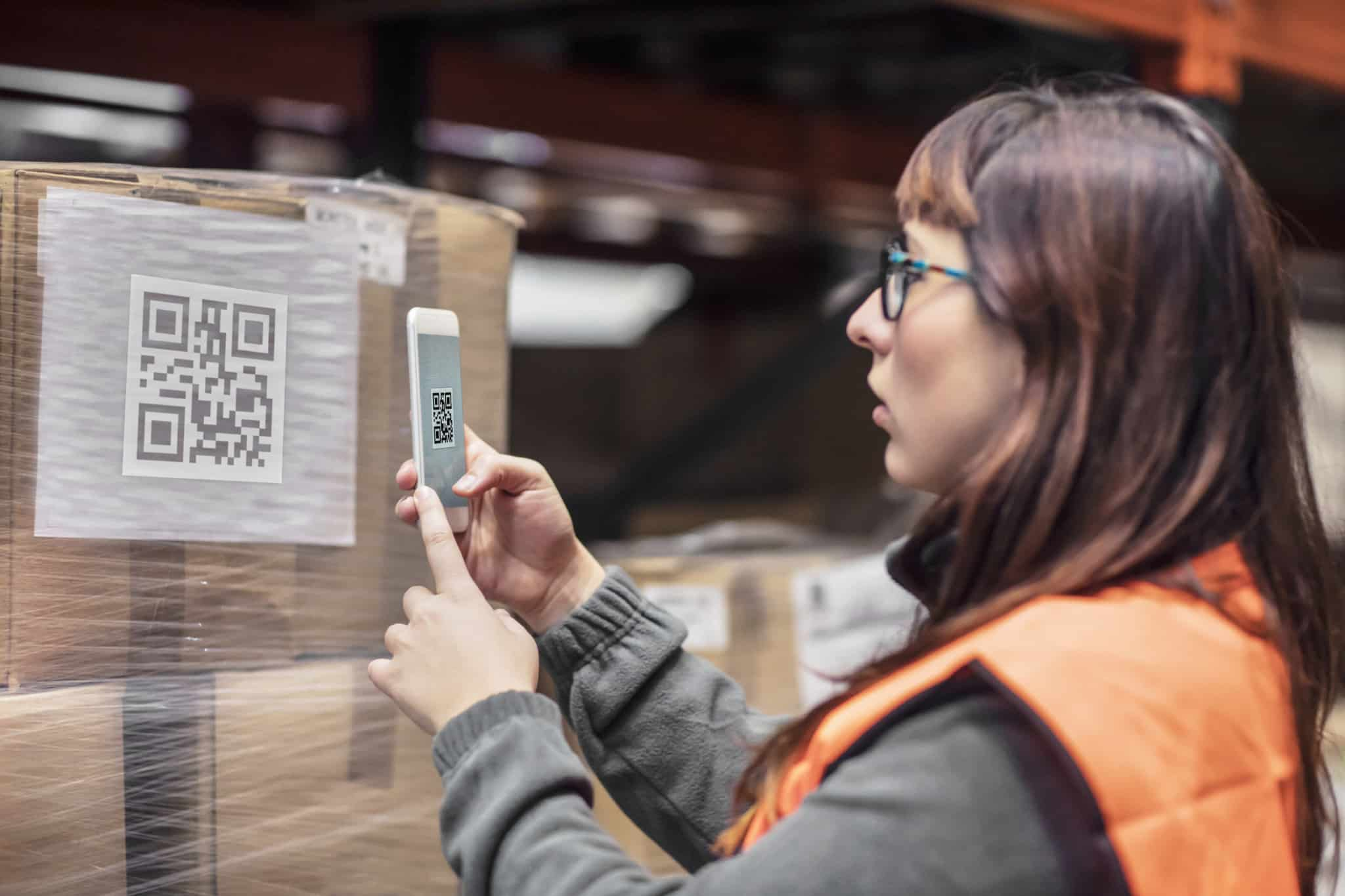 A woman in a visibility vest uses her phone to scan the QR code on a package.