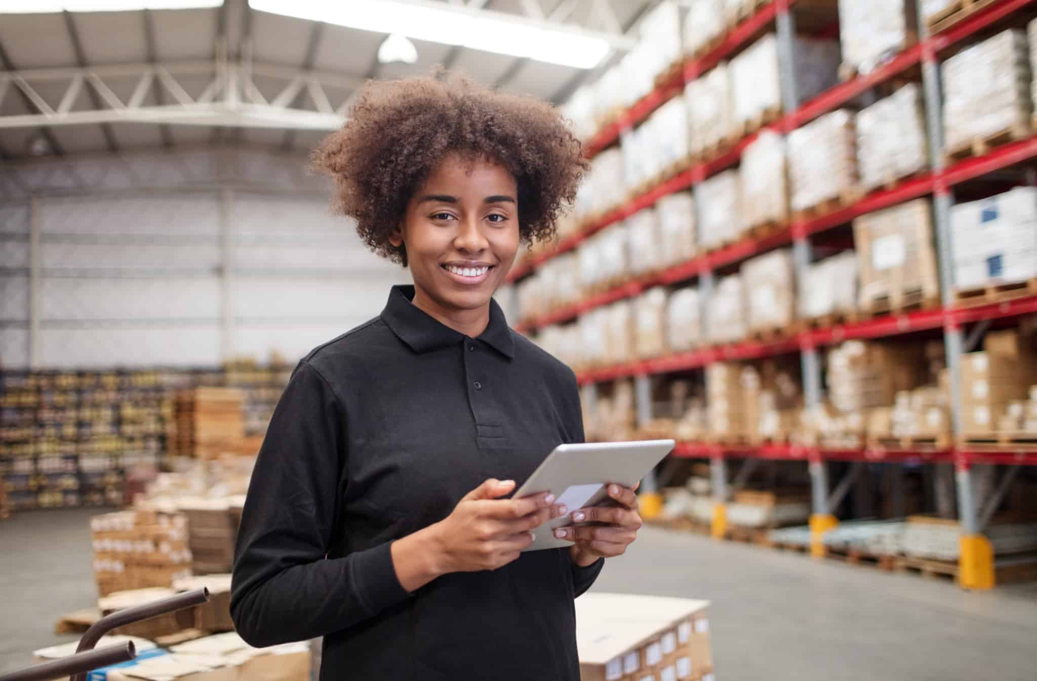 Female warehouse worker takes inventory on a tablet.