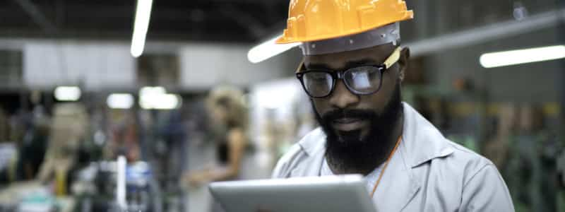 A man wearing a hardhat reviews information on a tablet while in a factory.