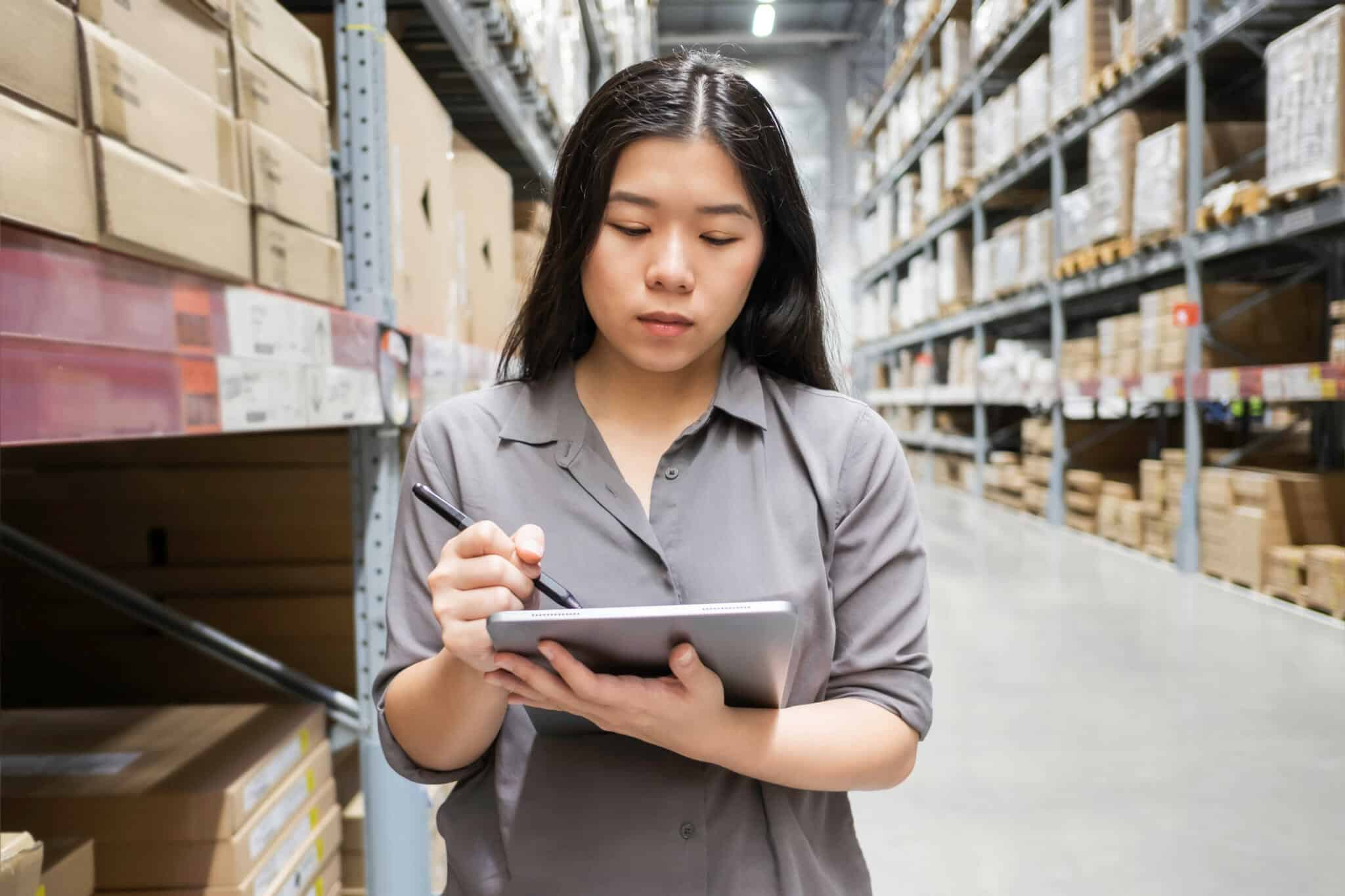 A woman conducts inventory counts in a warehouse.